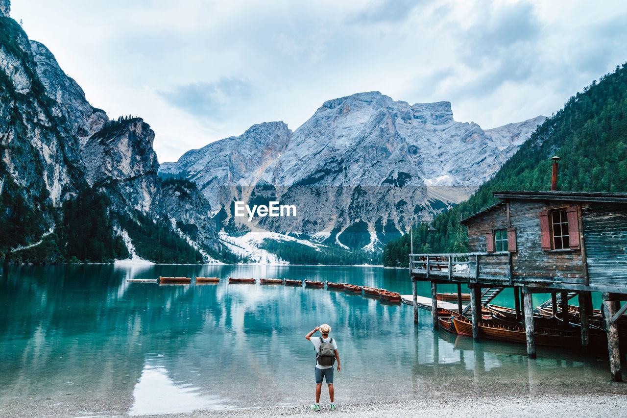 REAR VIEW OF PERSON ON LAKE AGAINST MOUNTAINS