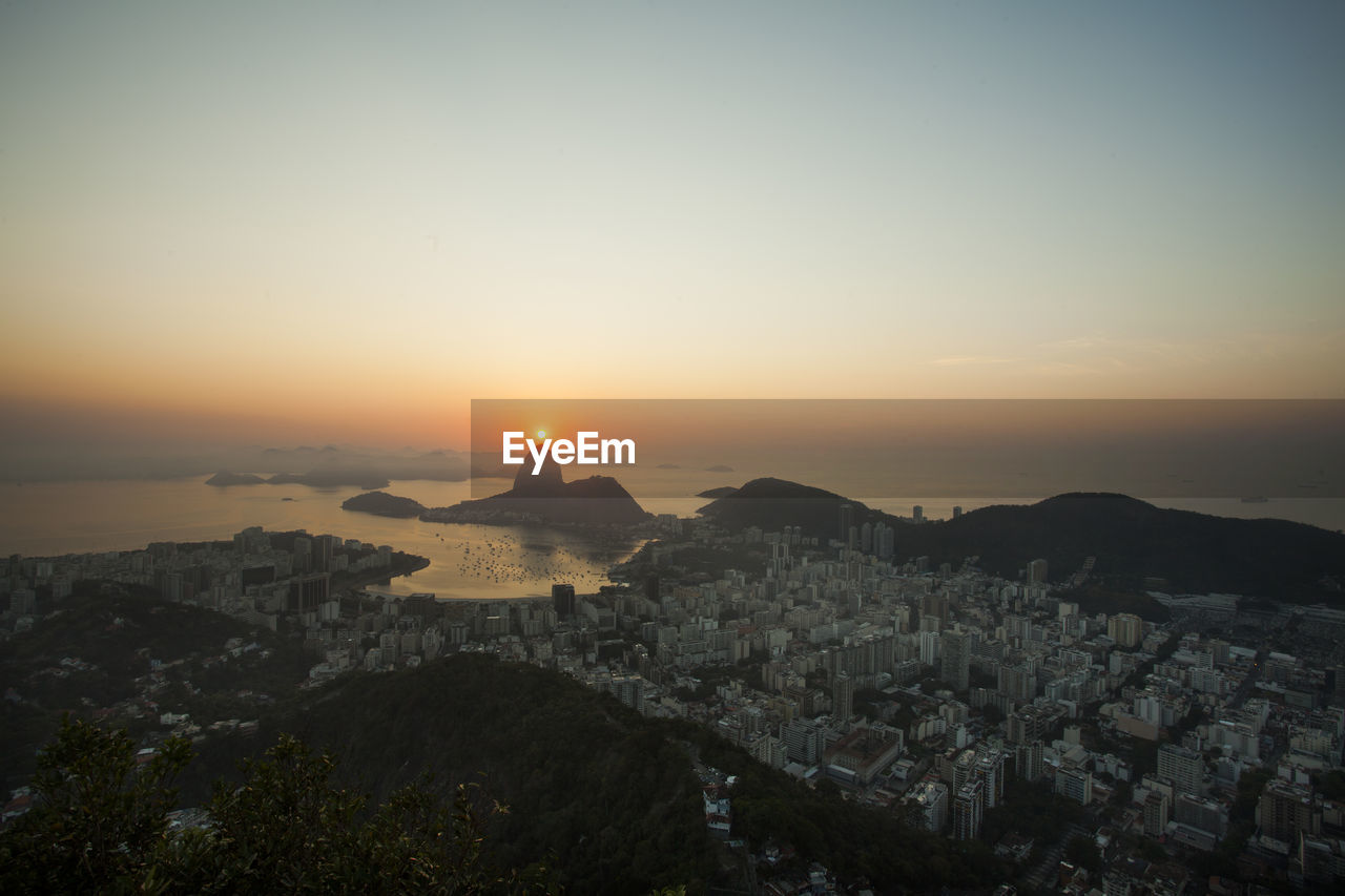 Cityscape By Sea Against Clear Sky During Sunset