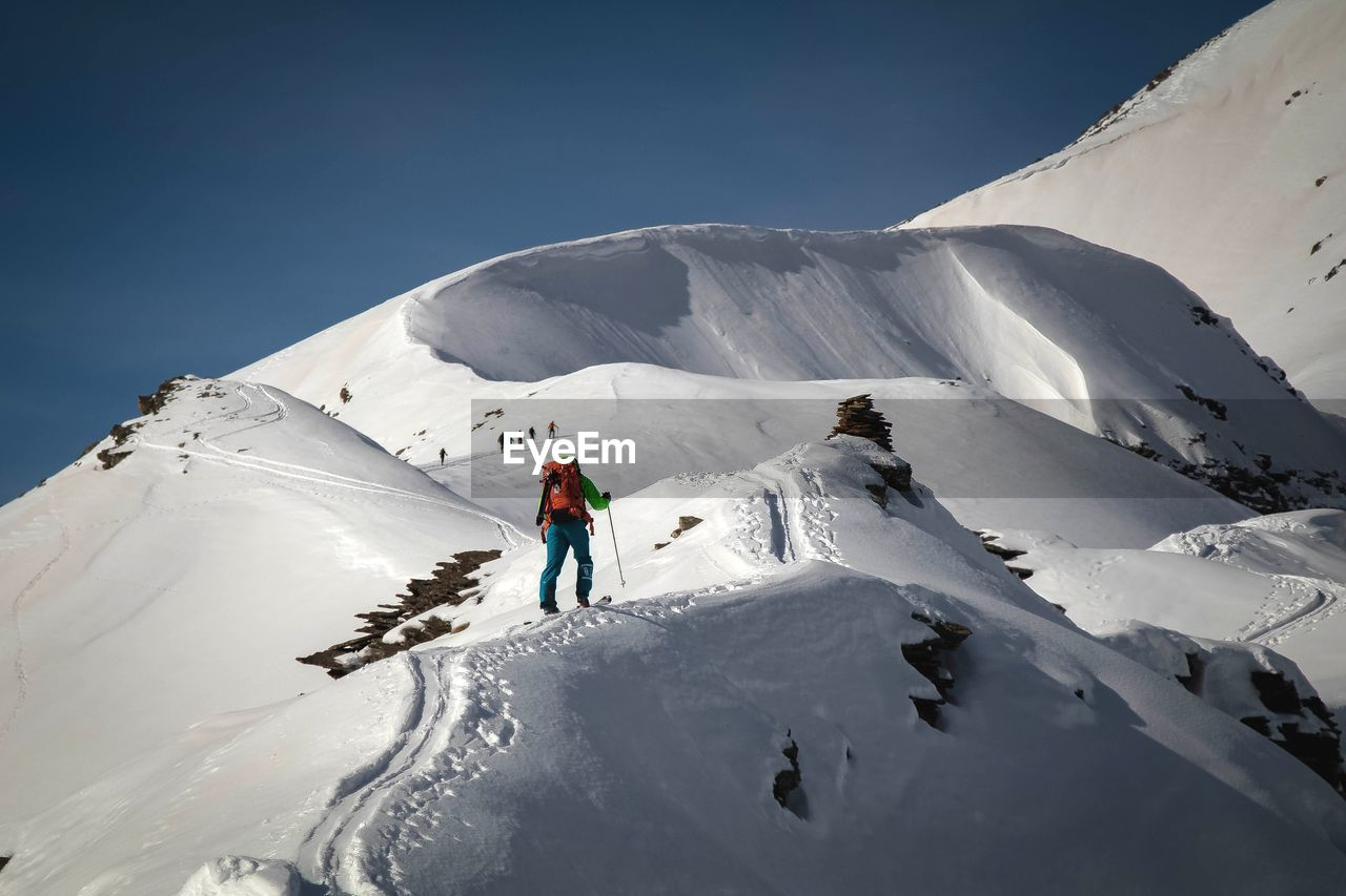 Low Angle View Of Hiker Hiking On Snowcapped Mountain