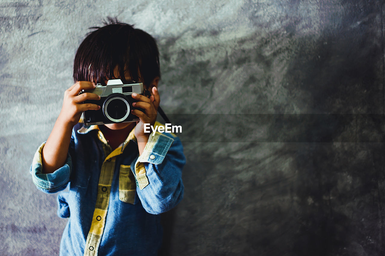 camera - photographic equipment, photography themes, photographing, one person, real people, holding, activity, leisure activity, technology, photographic equipment, casual clothing, lifestyles, front view, camera, standing, digital camera, wall - building feature, men, photographer, outdoors, digital single-lens reflex camera