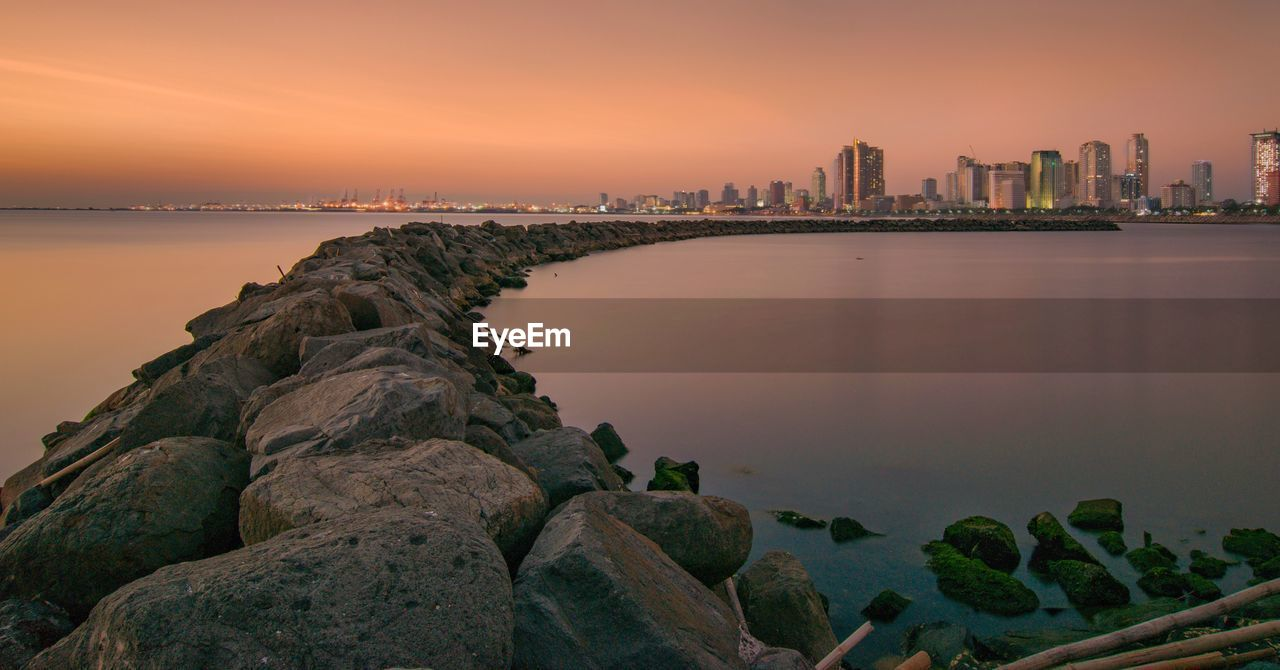 sky, water, built structure, building exterior, architecture, sunset, rock, sea, rock - object, solid, nature, city, scenics - nature, building, urban skyline, beauty in nature, no people, tranquil scene, tranquility, skyscraper, office building exterior, cityscape, outdoors, bay