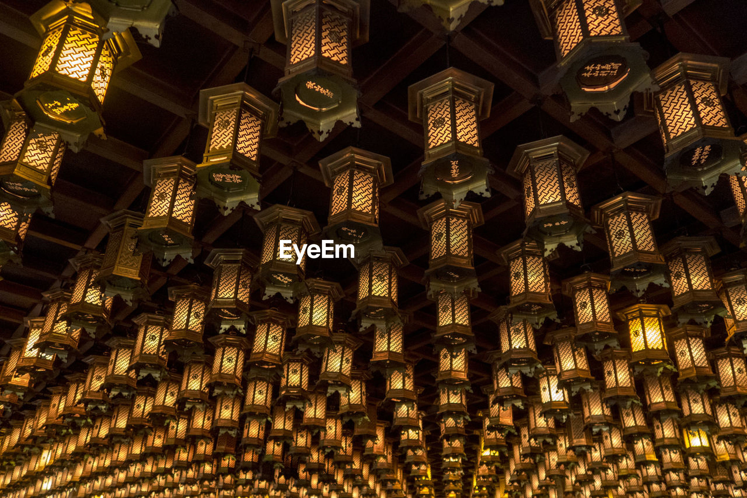 low angle view, full frame, no people, indoors, pattern, backgrounds, abundance, built structure, large group of objects, architecture, repetition, hanging, place of worship, decoration, lighting equipment, belief, design, creativity, illuminated, religion, ceiling, ornate