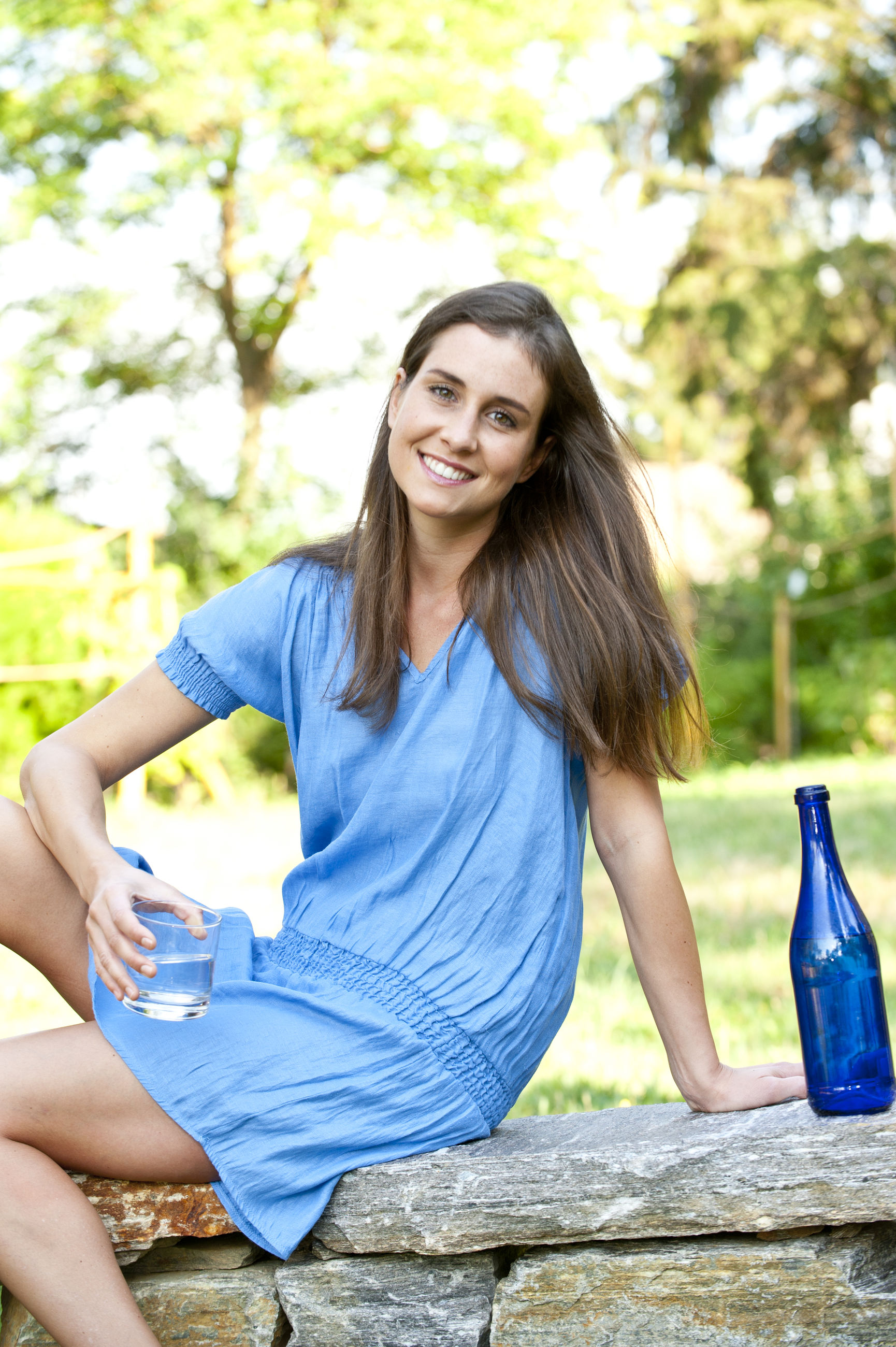 Portrait of smiling young woman holding glass on retaining wall at park