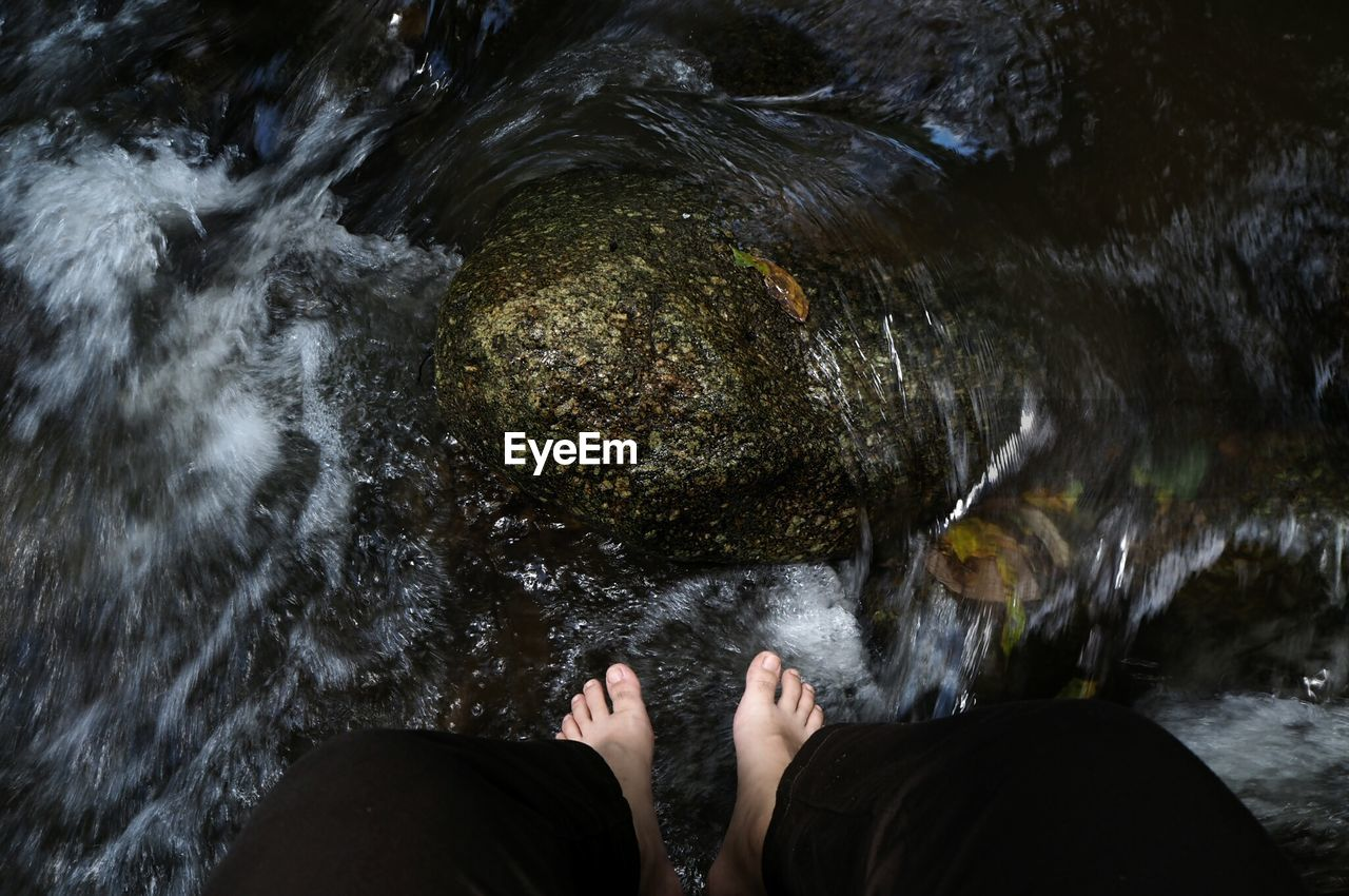 low section, real people, water, human leg, personal perspective, body part, human body part, barefoot, rock, one person, rock - object, high angle view, standing, nature, leisure activity, lifestyles, solid, day, human foot, outdoors, flowing water