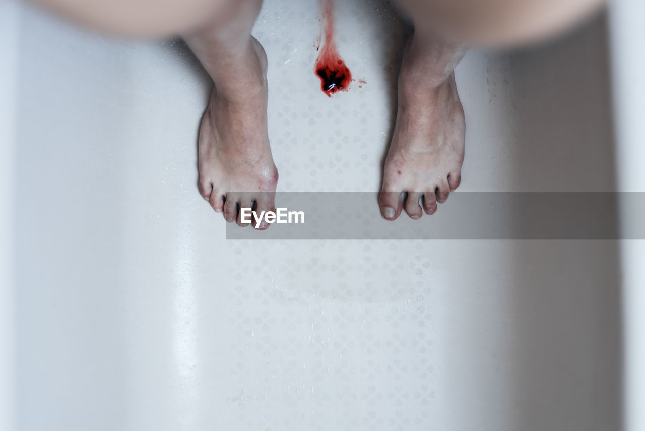 Directly above shot of blood amidst woman standing in bathtub