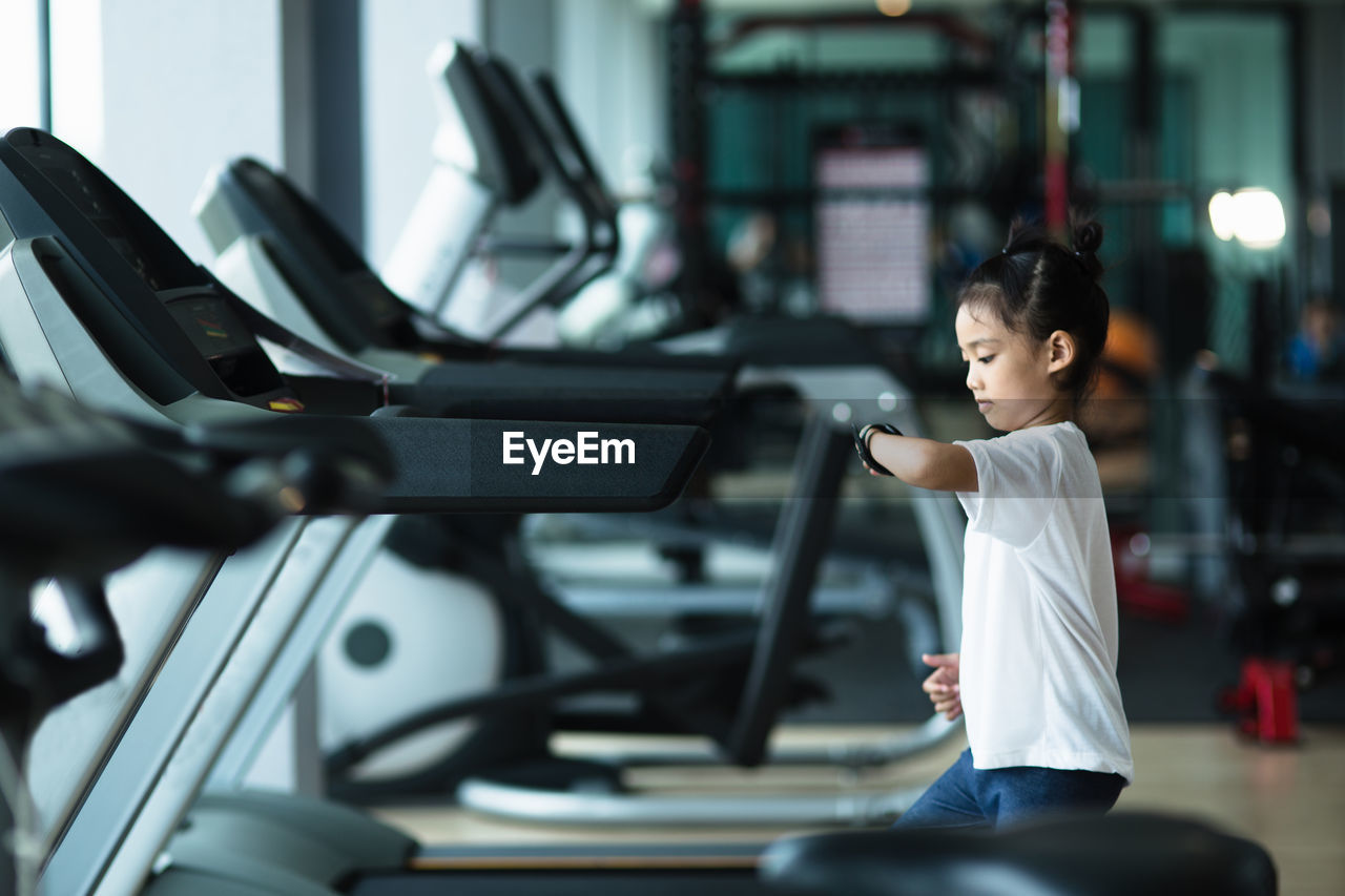 Side view of girl looking at smartwatch in gym