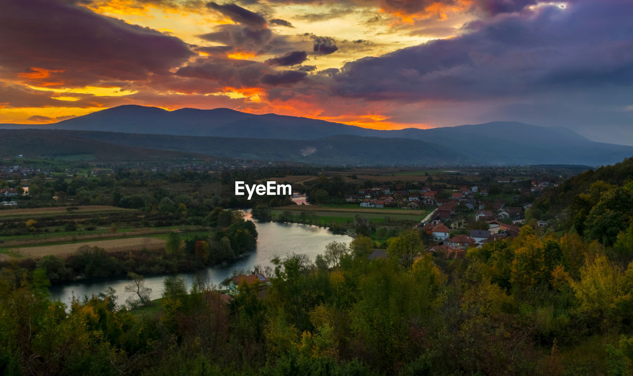 SCENIC VIEW OF RIVER AND LANDSCAPE AGAINST SKY DURING SUNSET