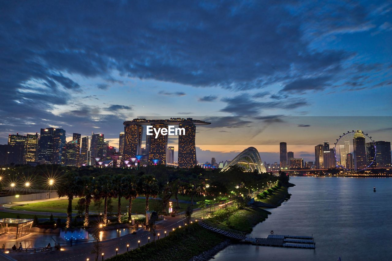 architecture, skyscraper, building exterior, built structure, city, sky, modern, cityscape, illuminated, urban skyline, water, cloud - sky, travel destinations, outdoors, no people, night, tree