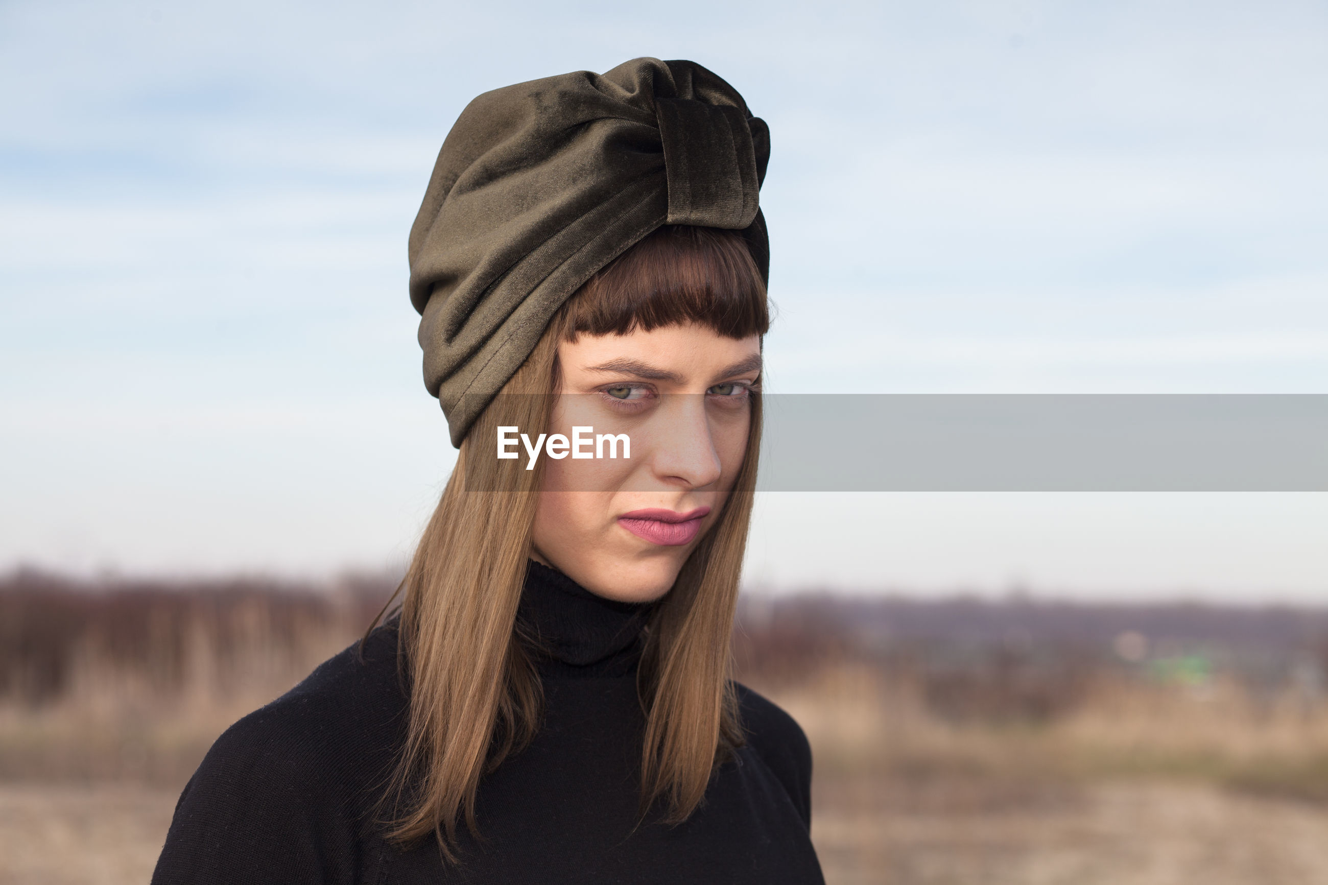 Portrait of young woman wearing headscarf against sky