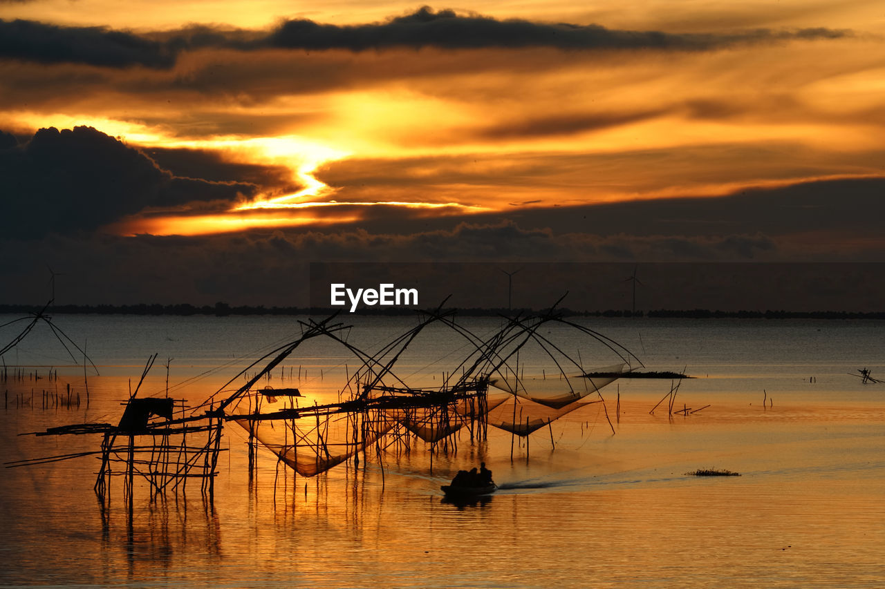 sky, sunset, water, cloud - sky, scenics - nature, beauty in nature, sea, orange color, waterfront, tranquility, tranquil scene, idyllic, nature, horizon over water, fishing, fishing net, horizon, no people, silhouette, fishing industry, outdoors