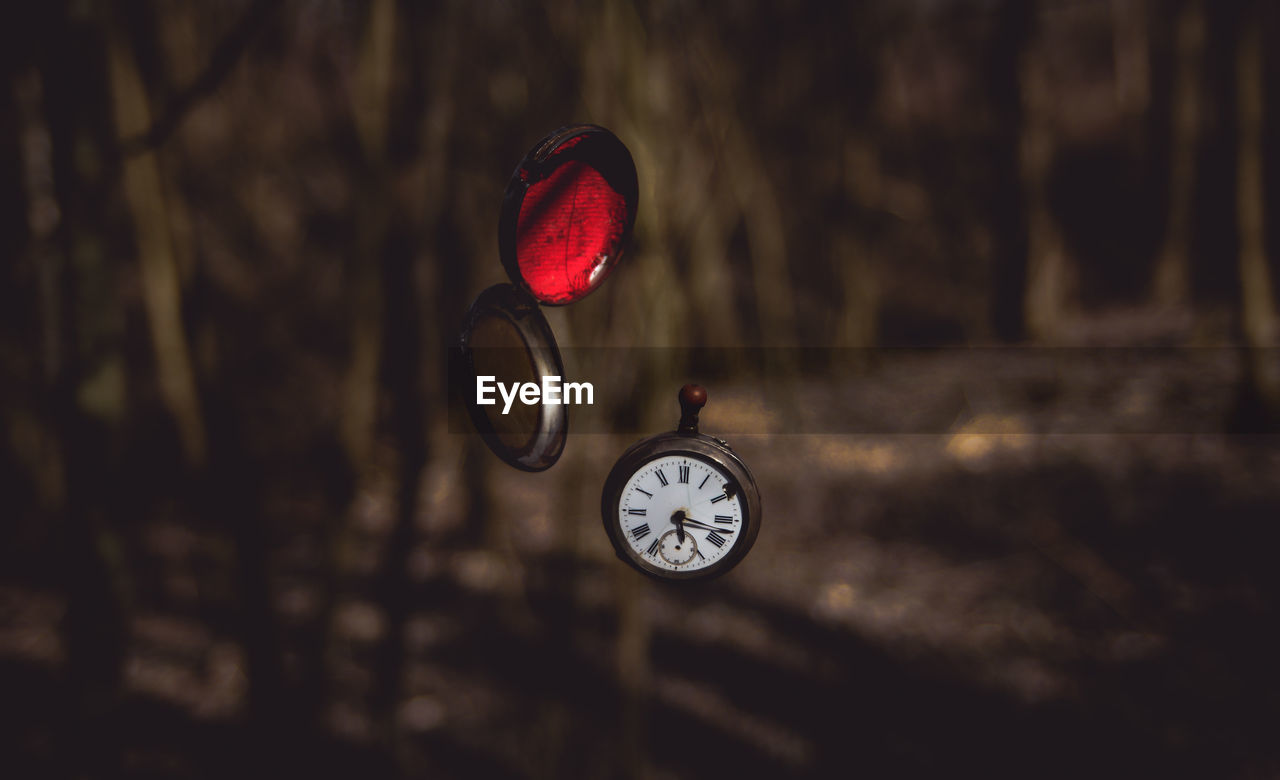Close-up of pocket watch levitating in forest