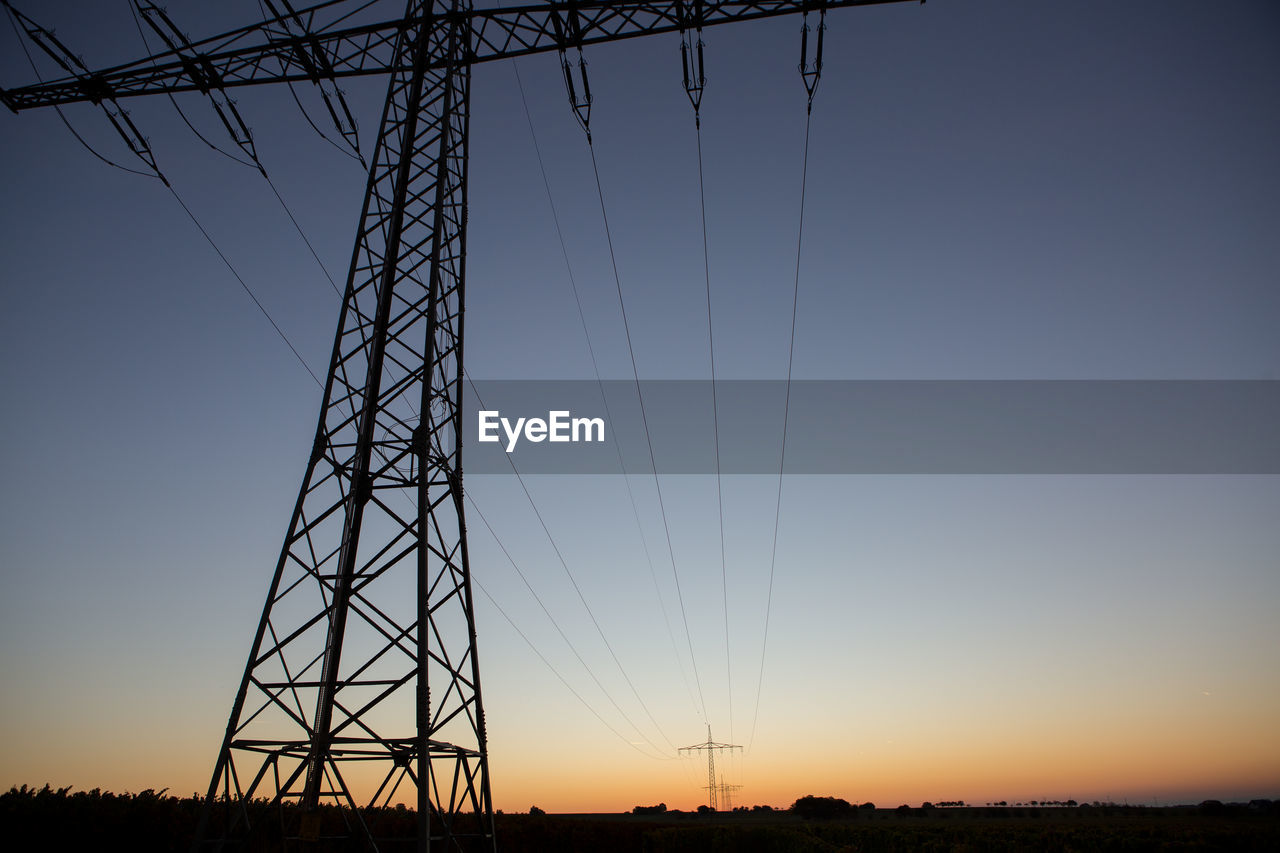 sky, electricity, cable, technology, connection, fuel and power generation, electricity pylon, power line, power supply, sunset, low angle view, nature, no people, silhouette, clear sky, orange color, metal, outdoors, built structure, dusk, complexity, electrical equipment