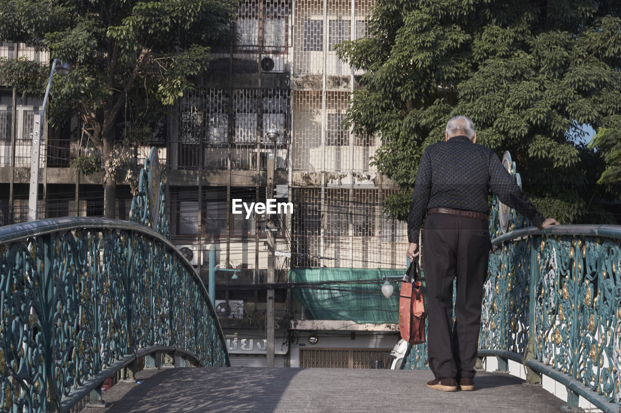 Rear view of old man on bridge