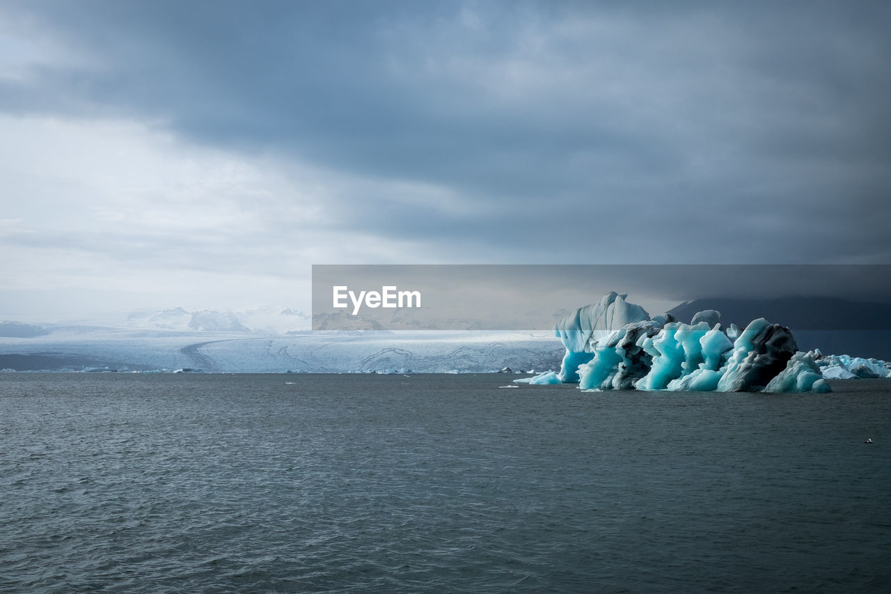 Scenic view of icebergs melting in sea against sky during winter