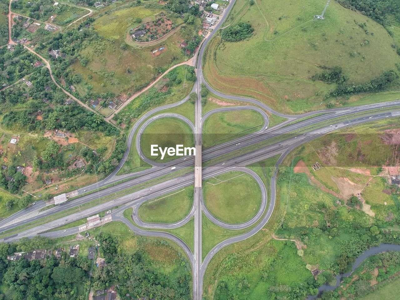 aerial view, road, transportation, environment, high angle view, landscape, plant, nature, no people, land, highway, green color, tree, city, scenics - nature, outdoors, day, field, beauty in nature, multiple lane highway