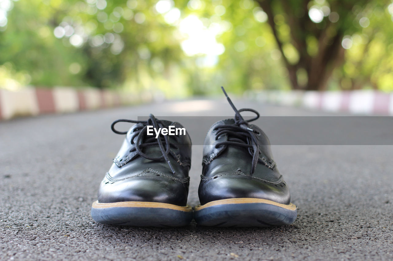 Close-up of shoes on road against trees