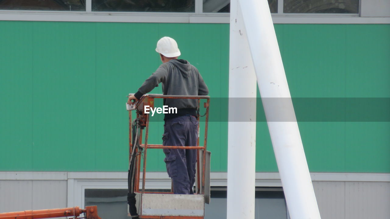 Rear view of construction worker standing on cherry picker against building