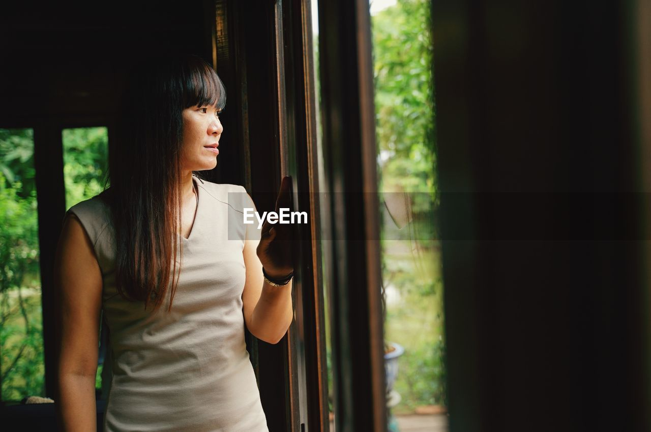 one person, real people, lifestyles, leisure activity, window, looking, standing, day, indoors, casual clothing, young adult, focus on foreground, nature, waist up, selective focus, women, young women, contemplation, hairstyle, teenager