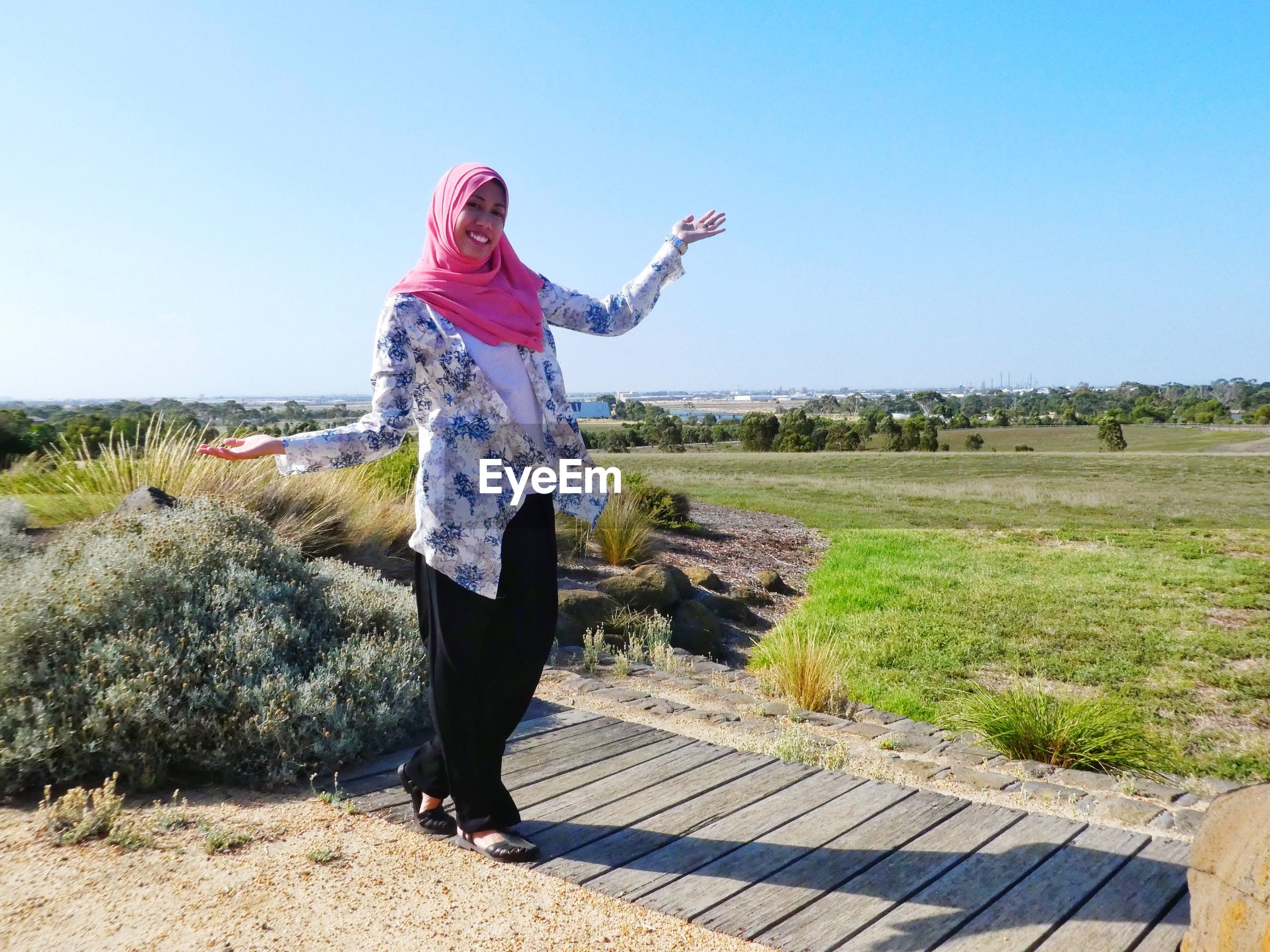 real people, one person, day, standing, full length, clear sky, field, sunlight, casual clothing, outdoors, nature, leisure activity, lifestyles, mature women, mature adult, sky, beauty in nature, grass, landscape, women, people