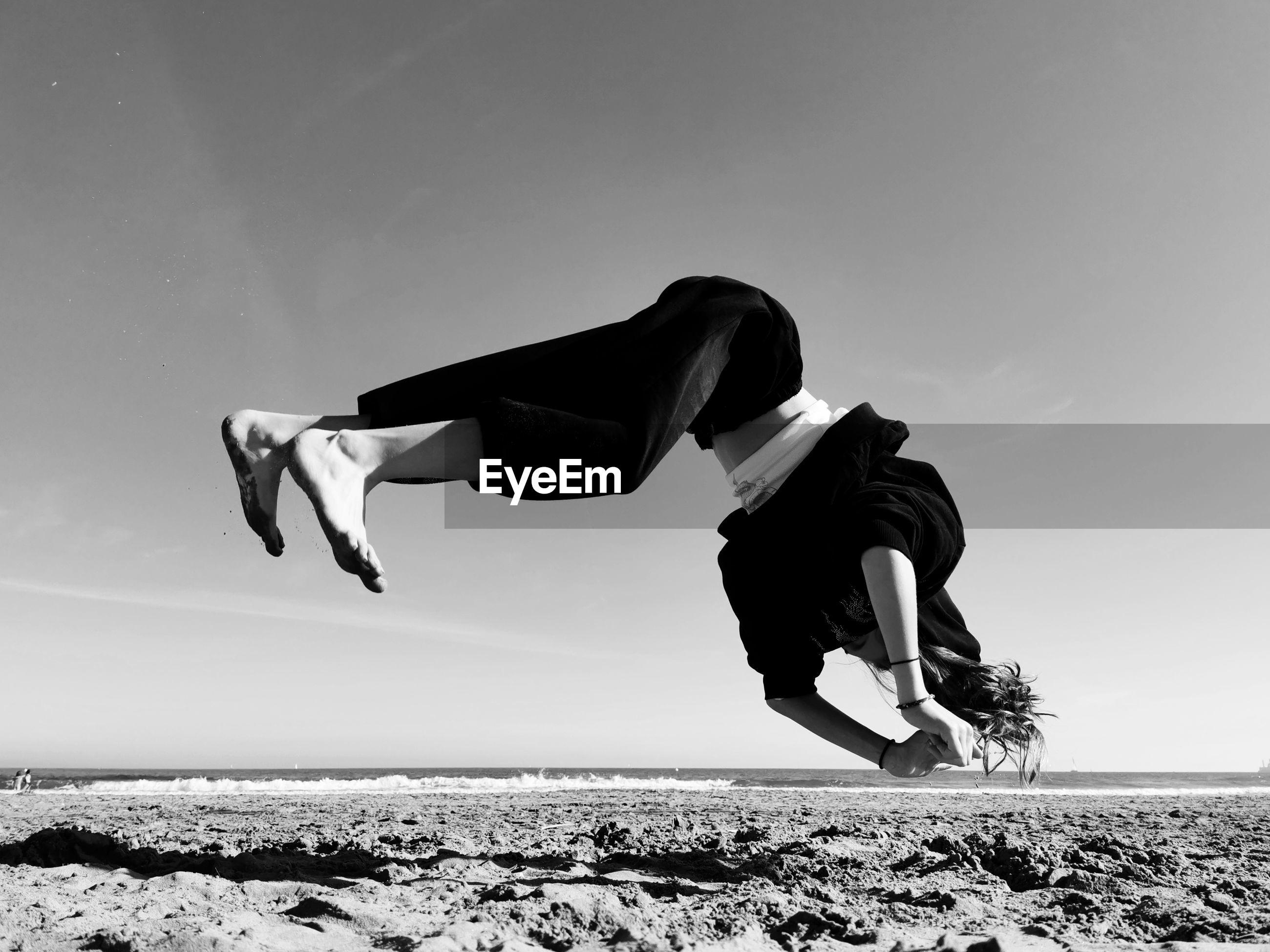 Full length of girl jumping against sky