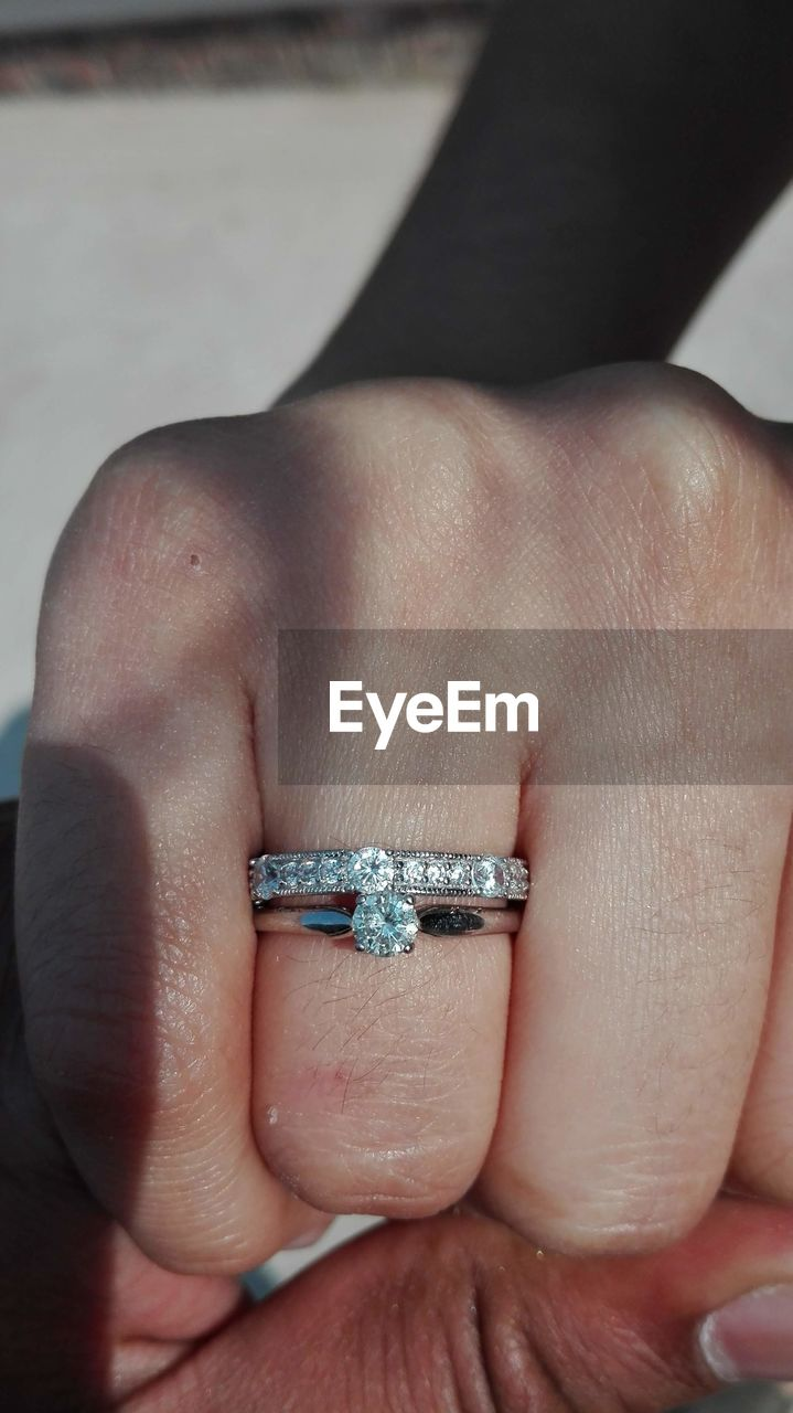 human hand, human body part, ring, jewelry, hand, body part, one person, real people, diamond - gemstone, close-up, finger, human finger, lifestyles, engagement ring, unrecognizable person, men, indoors, engagement, diamond ring, luxury, human limb, personal accessory