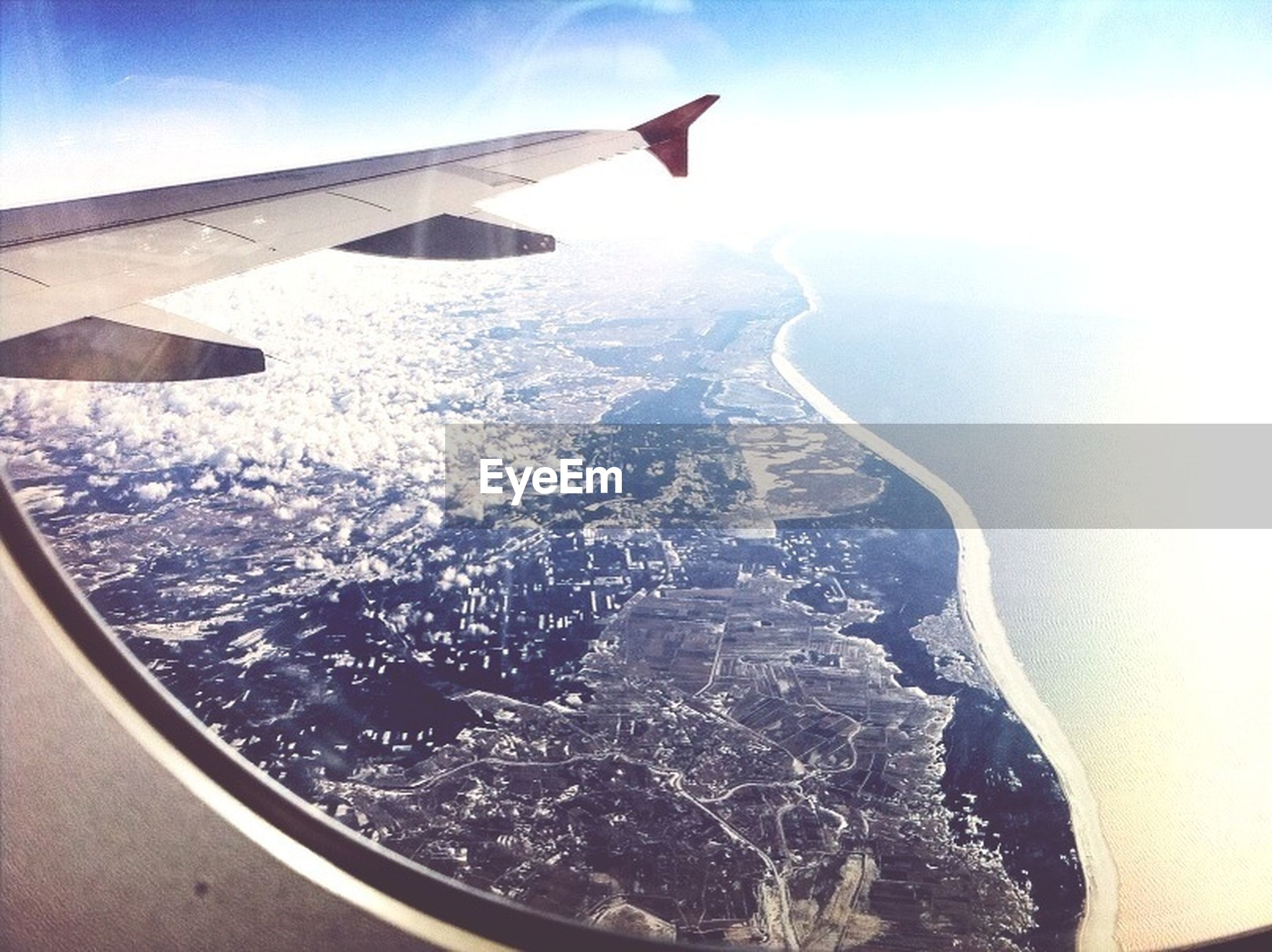 transportation, airplane, air vehicle, mode of transport, aircraft wing, part of, aerial view, cropped, flying, travel, mid-air, journey, on the move, vehicle part, vehicle interior, sky, window, scenics, sea, landscape