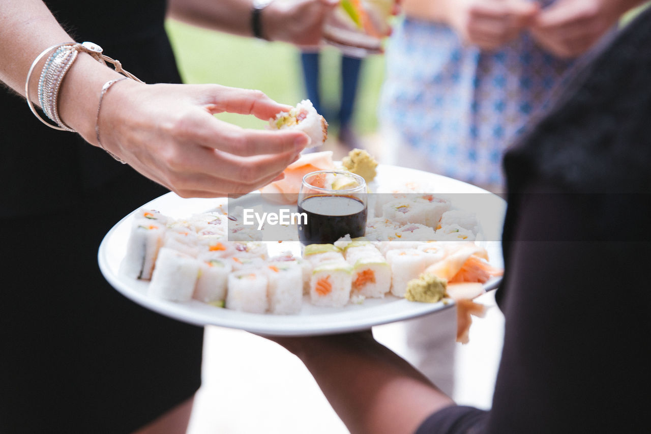 food and drink, food, holding, real people, hand, freshness, human hand, adult, midsection, ready-to-eat, women, two people, people, human body part, plate, lifestyles, table, indoors, focus on foreground, togetherness