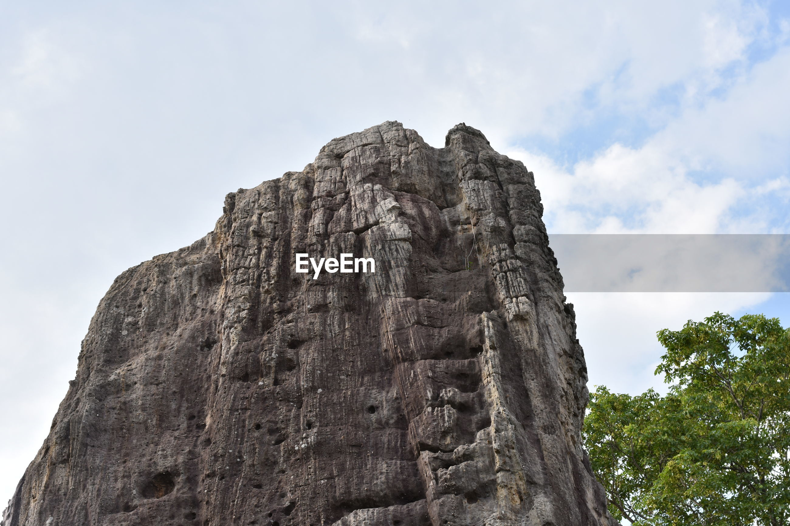 LOW ANGLE VIEW OF ROCK FORMATION BY MOUNTAIN AGAINST SKY