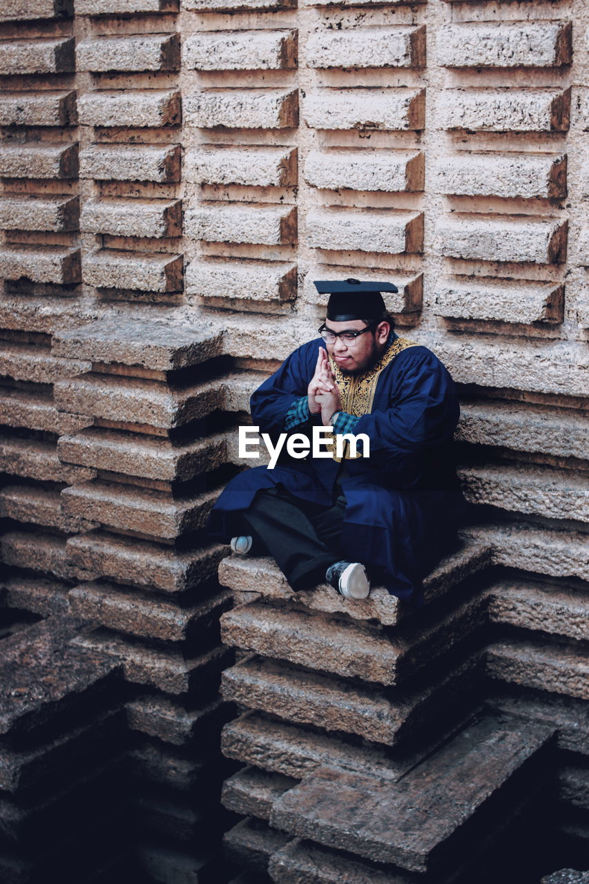 Man Wearing Mortar Board Sitting At Build Structure