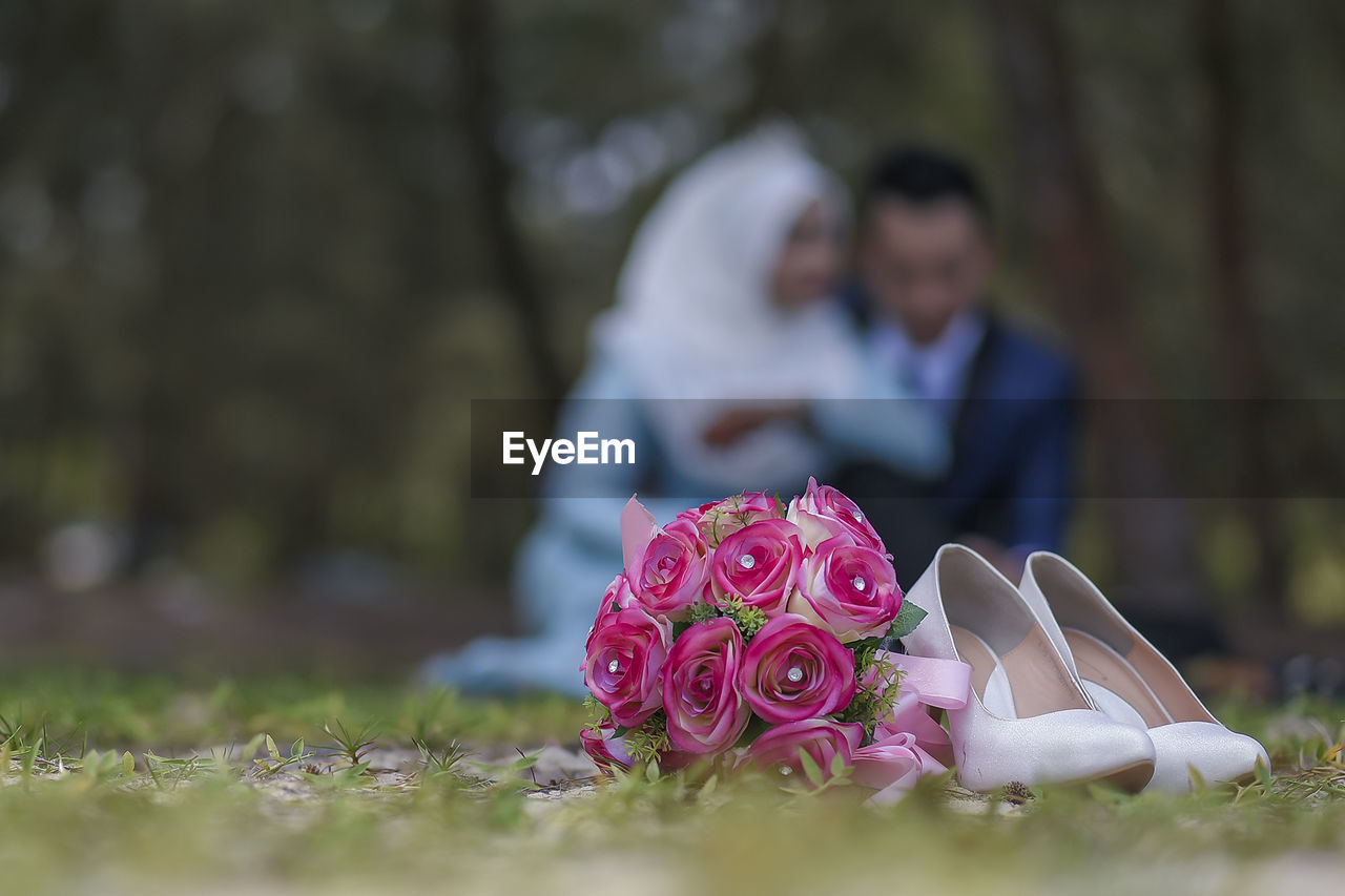 Close-up of rose bouquet and shoes against couple in park