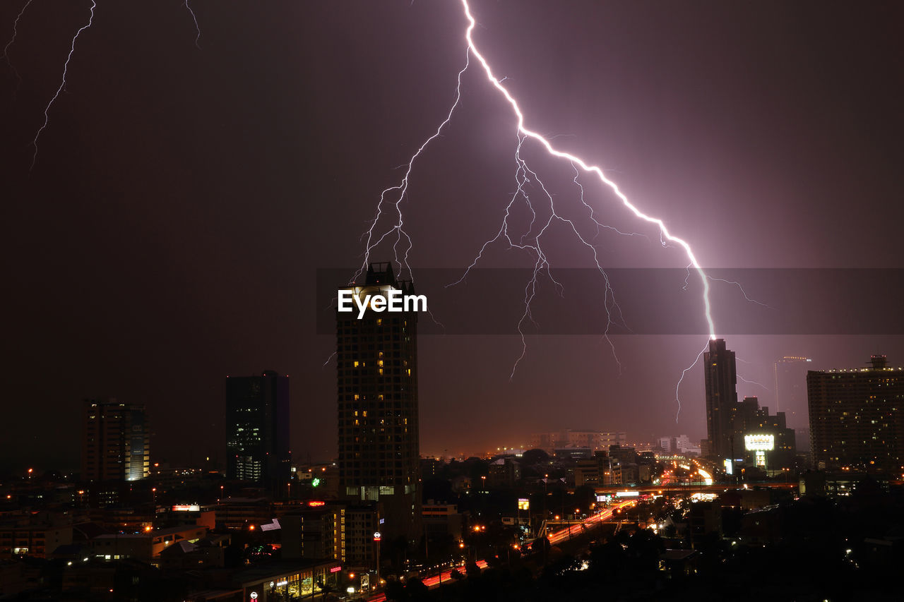 Illuminated buildings below lightning in dramatic sky at night