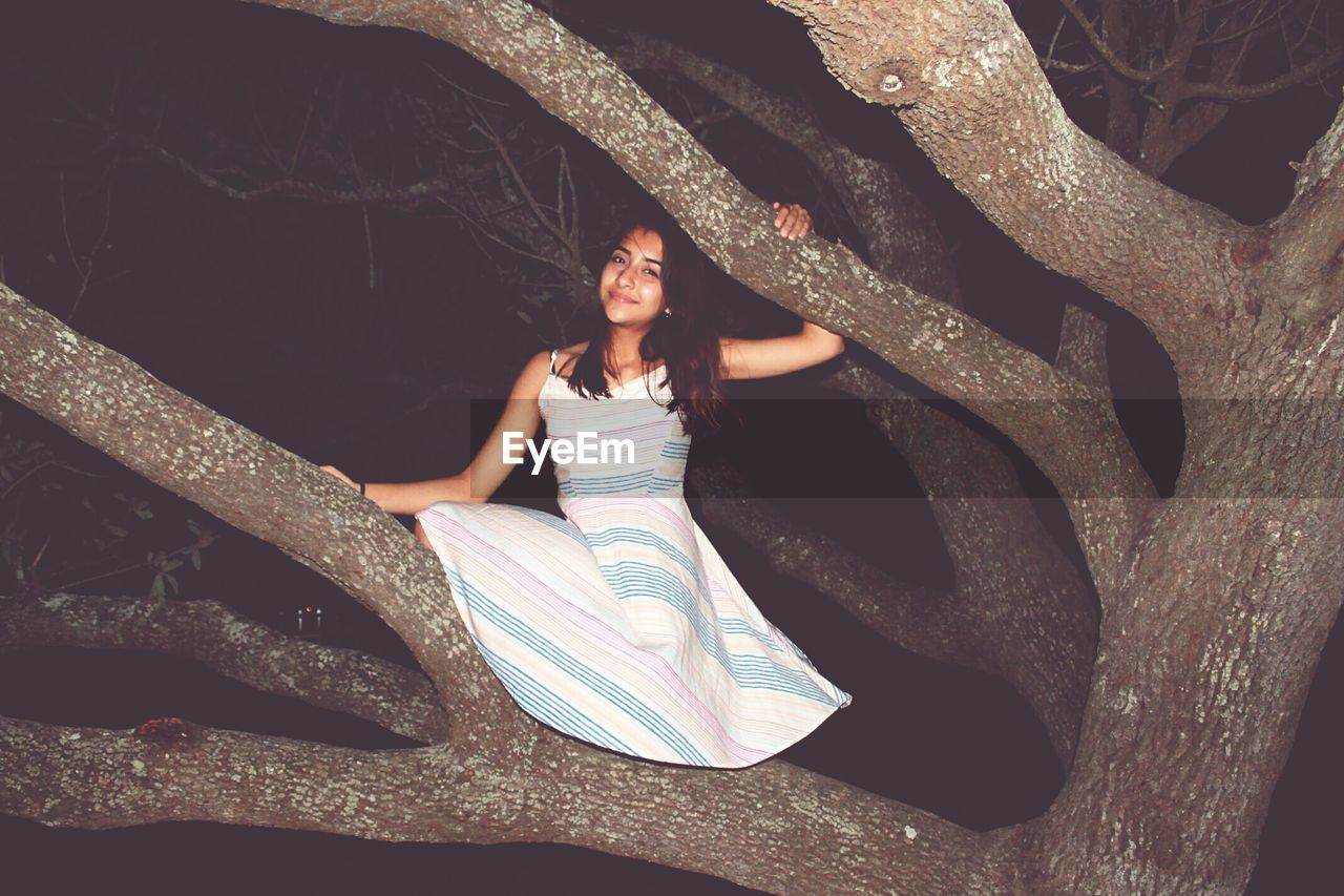 Portrait of young woman standing on tree at night