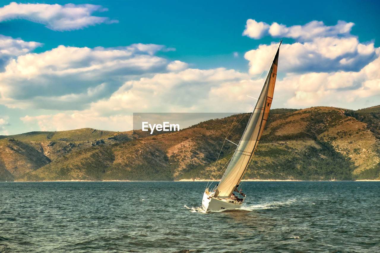 Boat Sailing On Sea By Mountain Against Sky