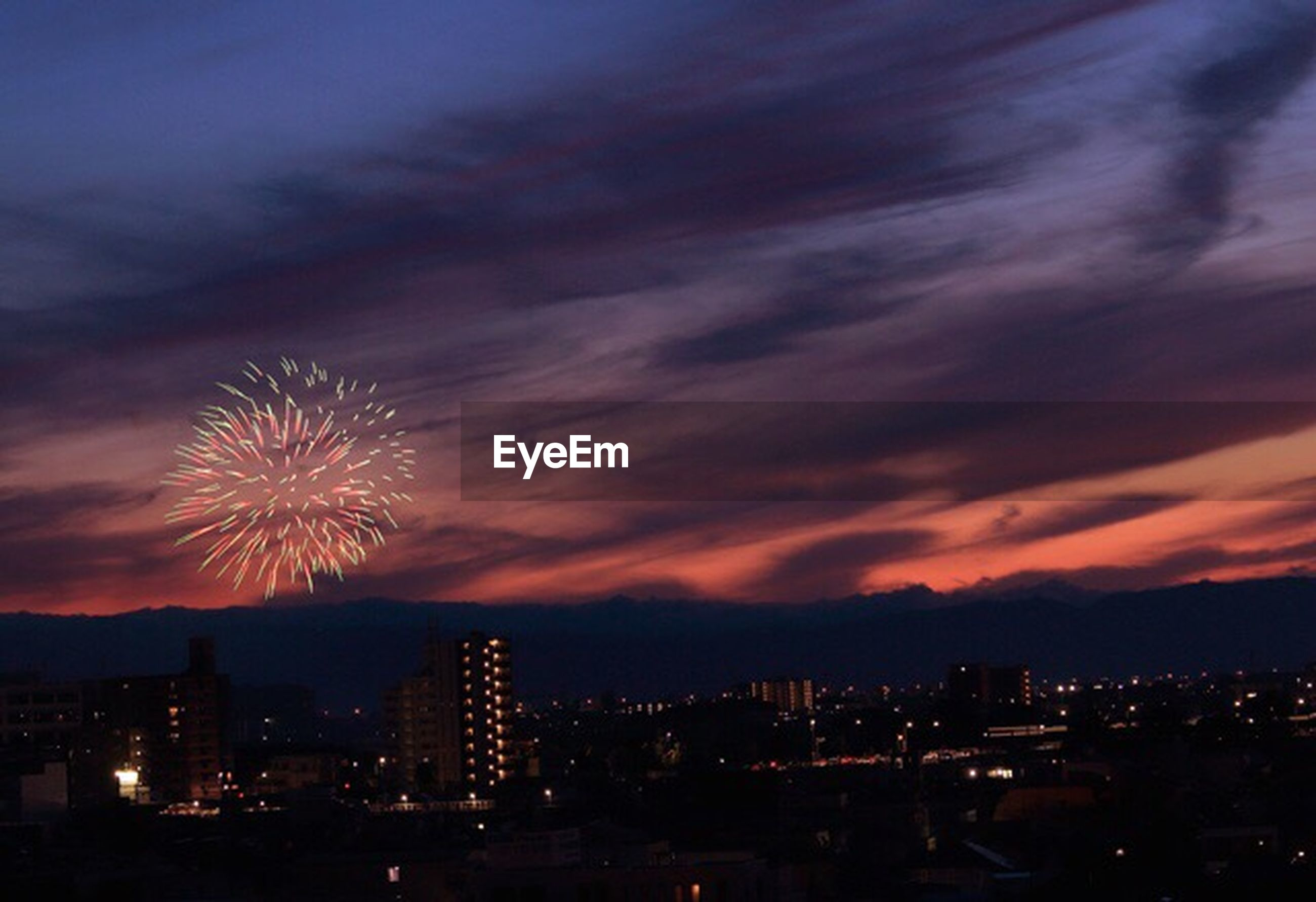 illuminated, night, sky, building exterior, cityscape, city, built structure, architecture, firework display, exploding, cloud - sky, long exposure, dramatic sky, glowing, outdoors, silhouette, firework - man made object, sunset, no people, dusk