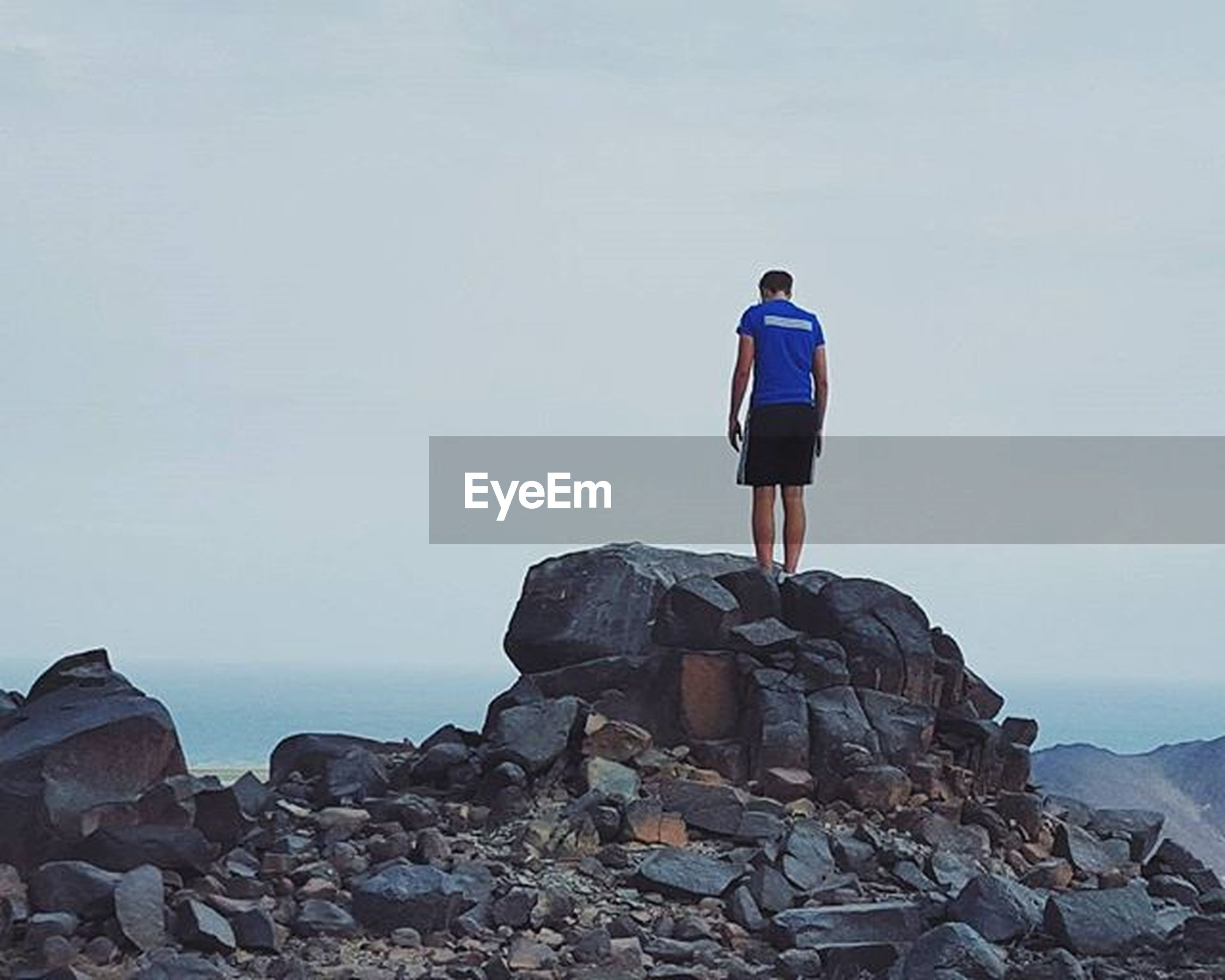 lifestyles, rock - object, leisure activity, full length, rear view, men, standing, copy space, sky, clear sky, sea, person, casual clothing, rock formation, horizon over water, rock, tranquility, tranquil scene