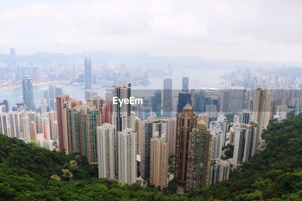 High Angle View Of Cityscape And River Against Cloudy Sky