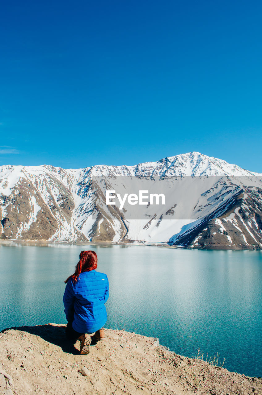 Rear view of young woman crouching by lake against mountain range