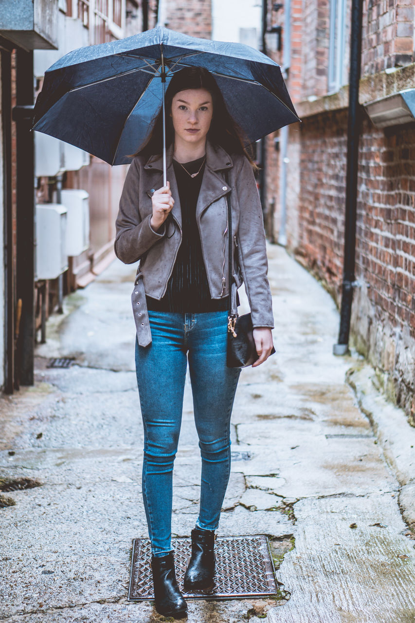 Full Length Portrait Of Young Woman Holding Umbrella While Standing In Alley
