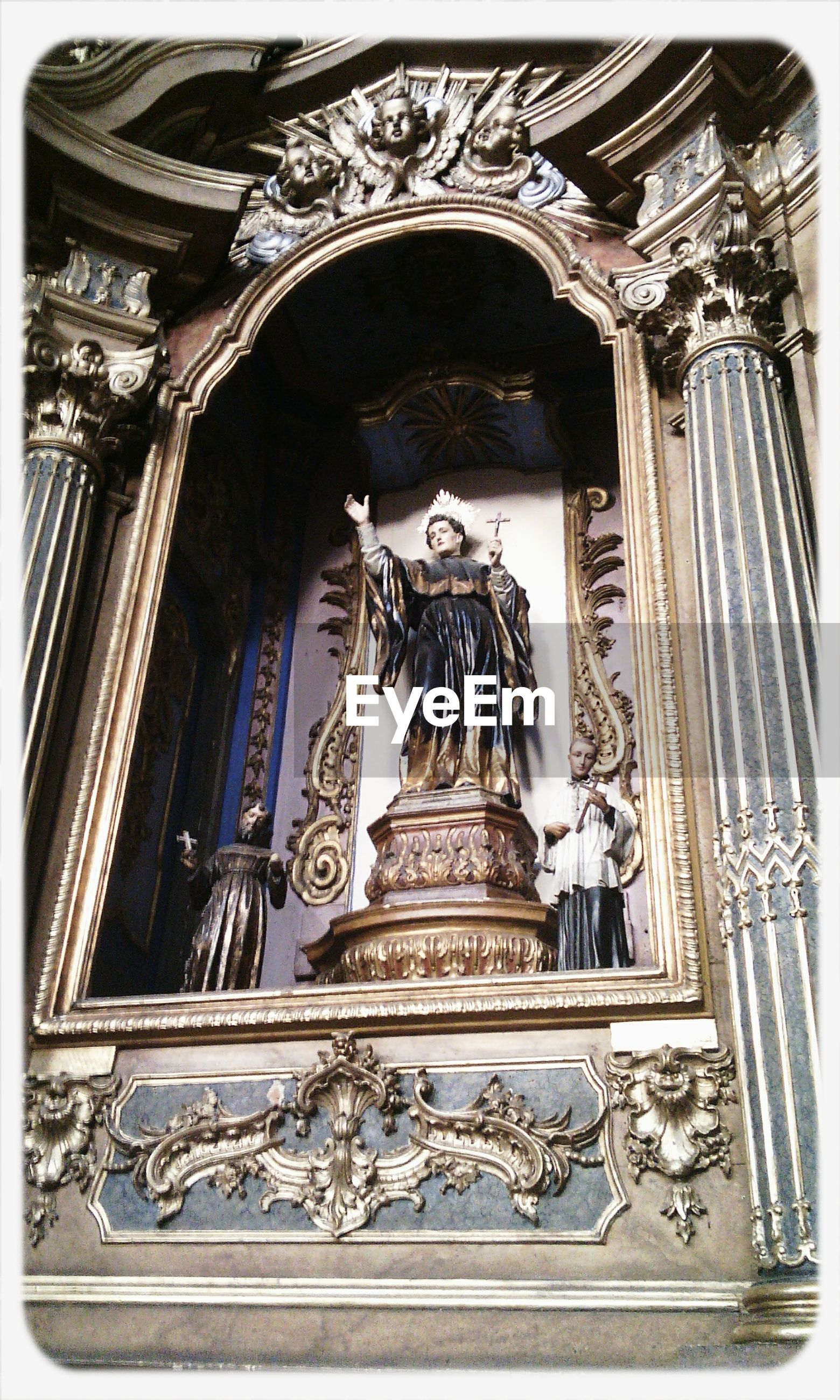 architecture, built structure, place of worship, transfer print, low angle view, religion, spirituality, church, ornate, building exterior, art and craft, arch, art, statue, auto post production filter, human representation, creativity, carving - craft product, sculpture