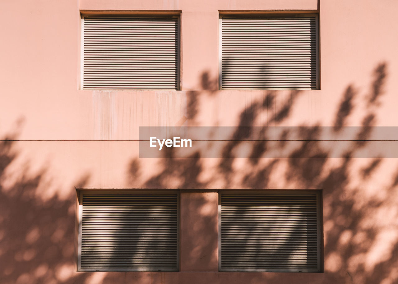 built structure, building exterior, architecture, sunlight, window, shadow, building, day, no people, nature, wall - building feature, shutter, outdoors, blinds, residential district, pattern, city, plant, house, low angle view