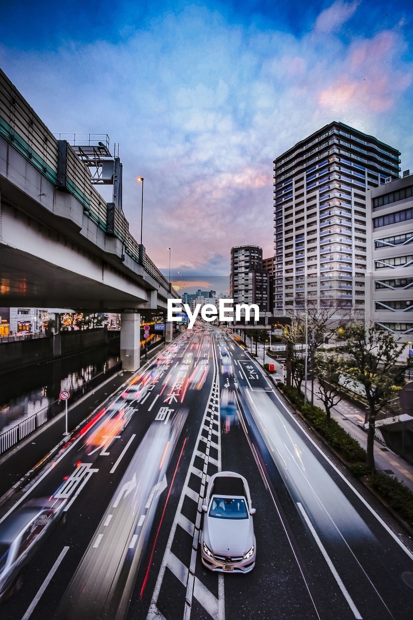 transportation, car, architecture, motor vehicle, built structure, road, building exterior, city, mode of transportation, sky, motion, street, land vehicle, cloud - sky, no people, traffic, nature, on the move, city life, long exposure, bridge - man made structure, light trail, city street, outdoors, multiple lane highway, office building exterior, skyscraper