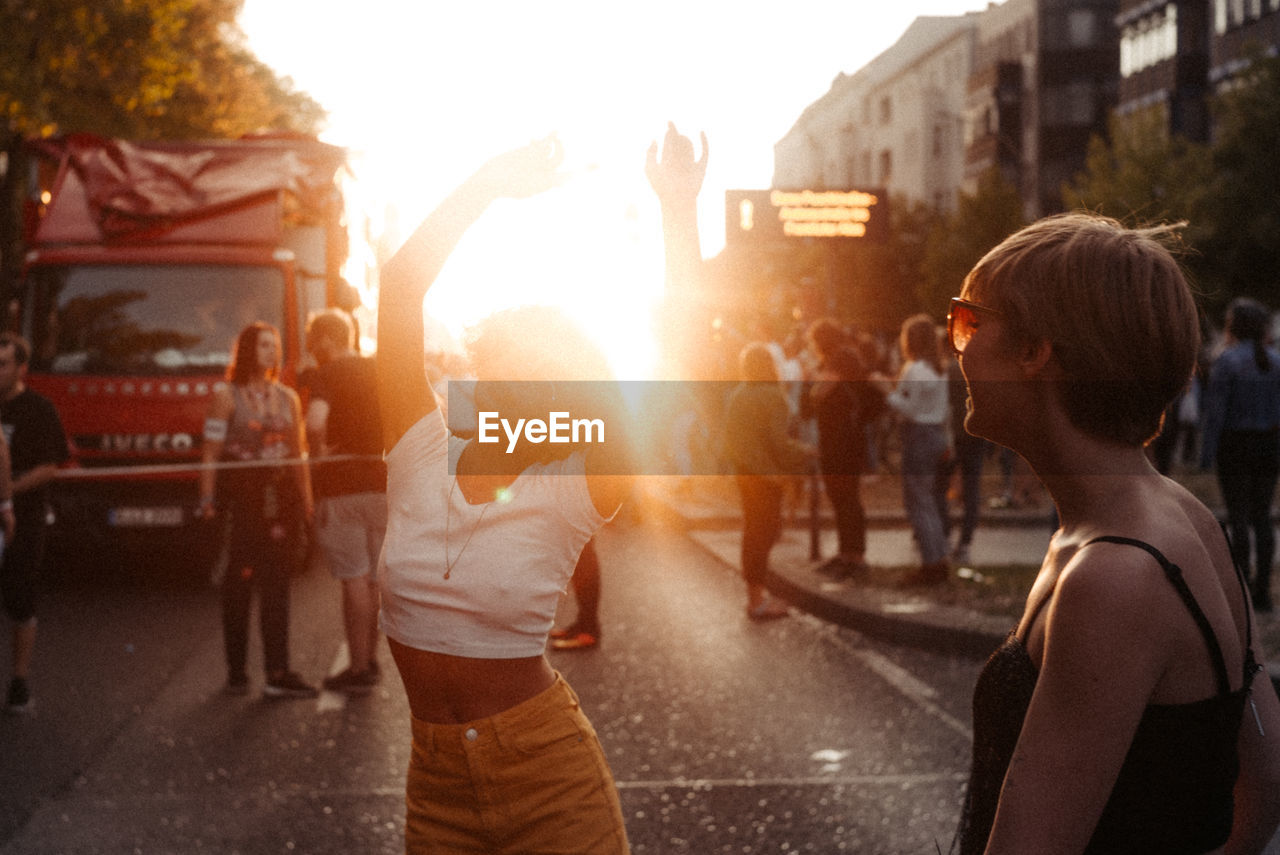 group of people, real people, city, women, street, architecture, men, transportation, people, adult, nature, incidental people, rear view, building exterior, crowd, road, lifestyles, leisure activity, city life, medium group of people, outdoors, lens flare, human arm