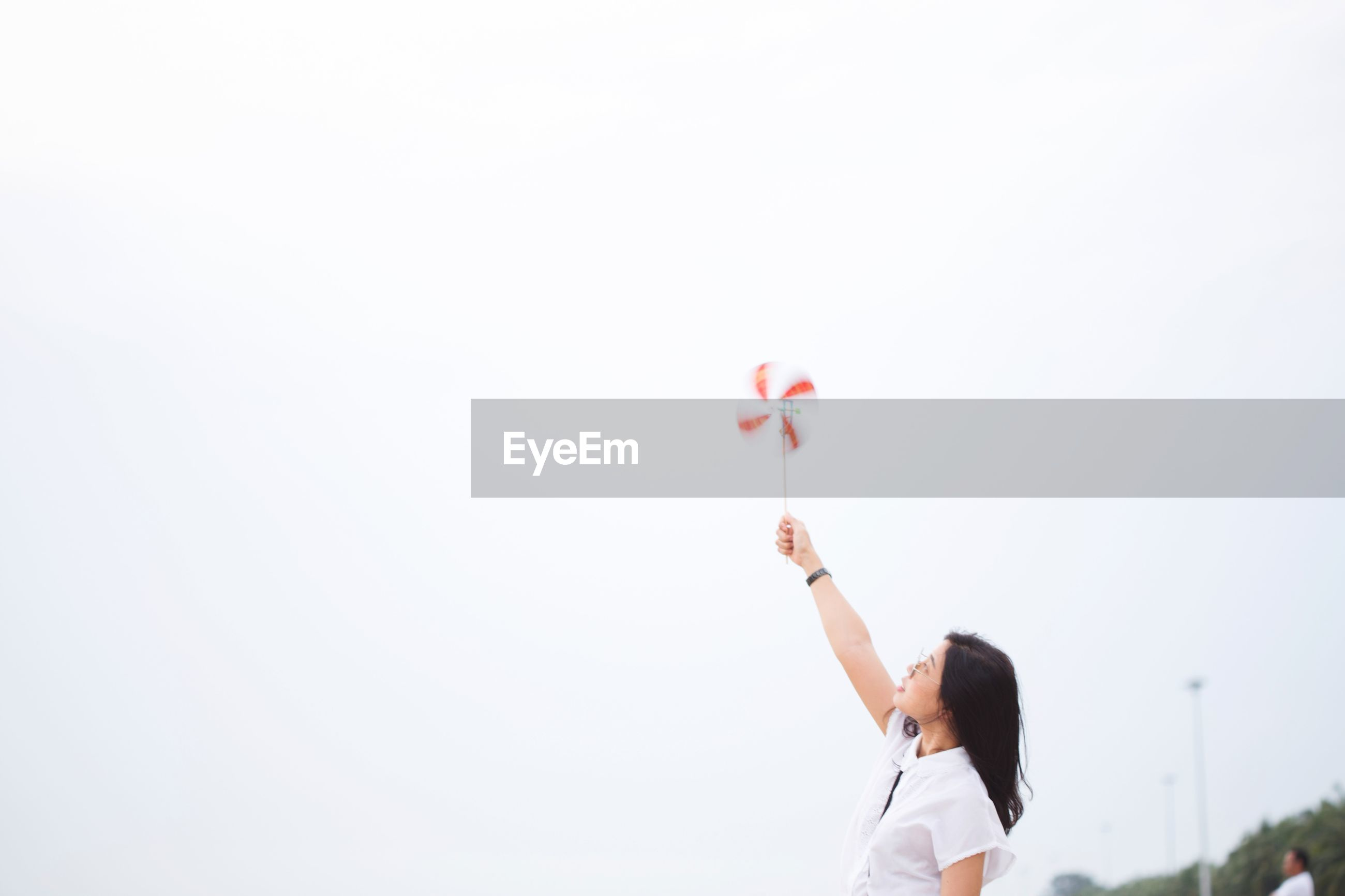 Woman holding pinwheel toy against clear sky