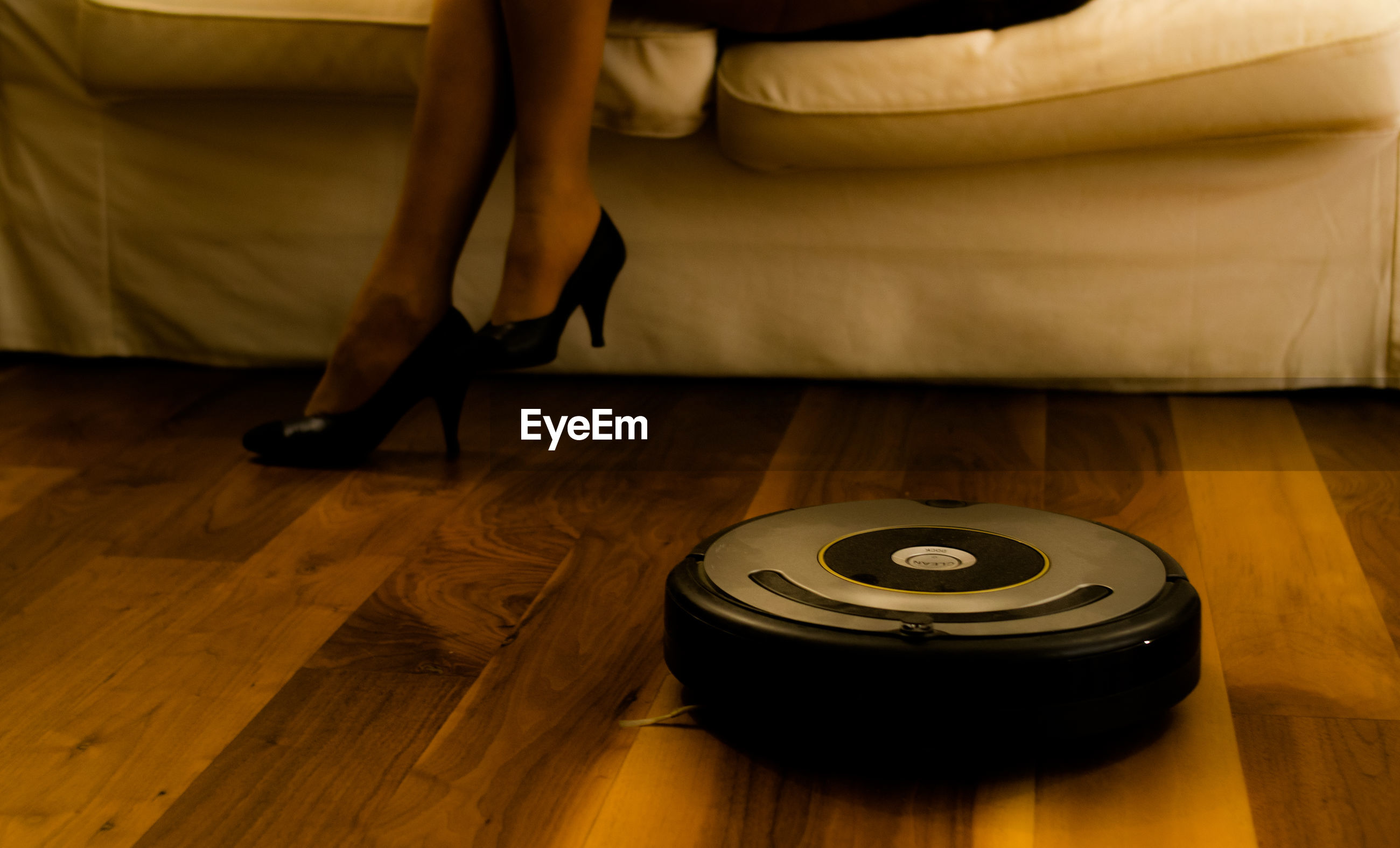 Low section of woman wearing shoes on hardwood floor by machine