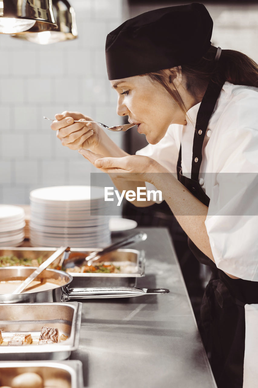 food and drink, occupation, uniform, real people, standing, food, holding, chef, preparation, indoors, kitchen, commercial kitchen, restaurant, freshness, one person, adult, business, mid adult, kitchen utensil, preparing food, food and drink establishment, skill