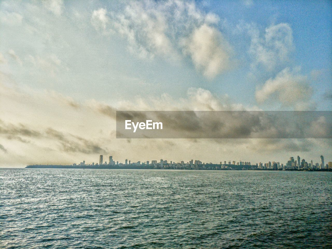 sky, sea, water, cloud - sky, beauty in nature, nature, waterfront, no people, tranquility, scenics, tranquil scene, outdoors, rippled, day, built structure, architecture, building exterior, horizon over water, cityscape, city
