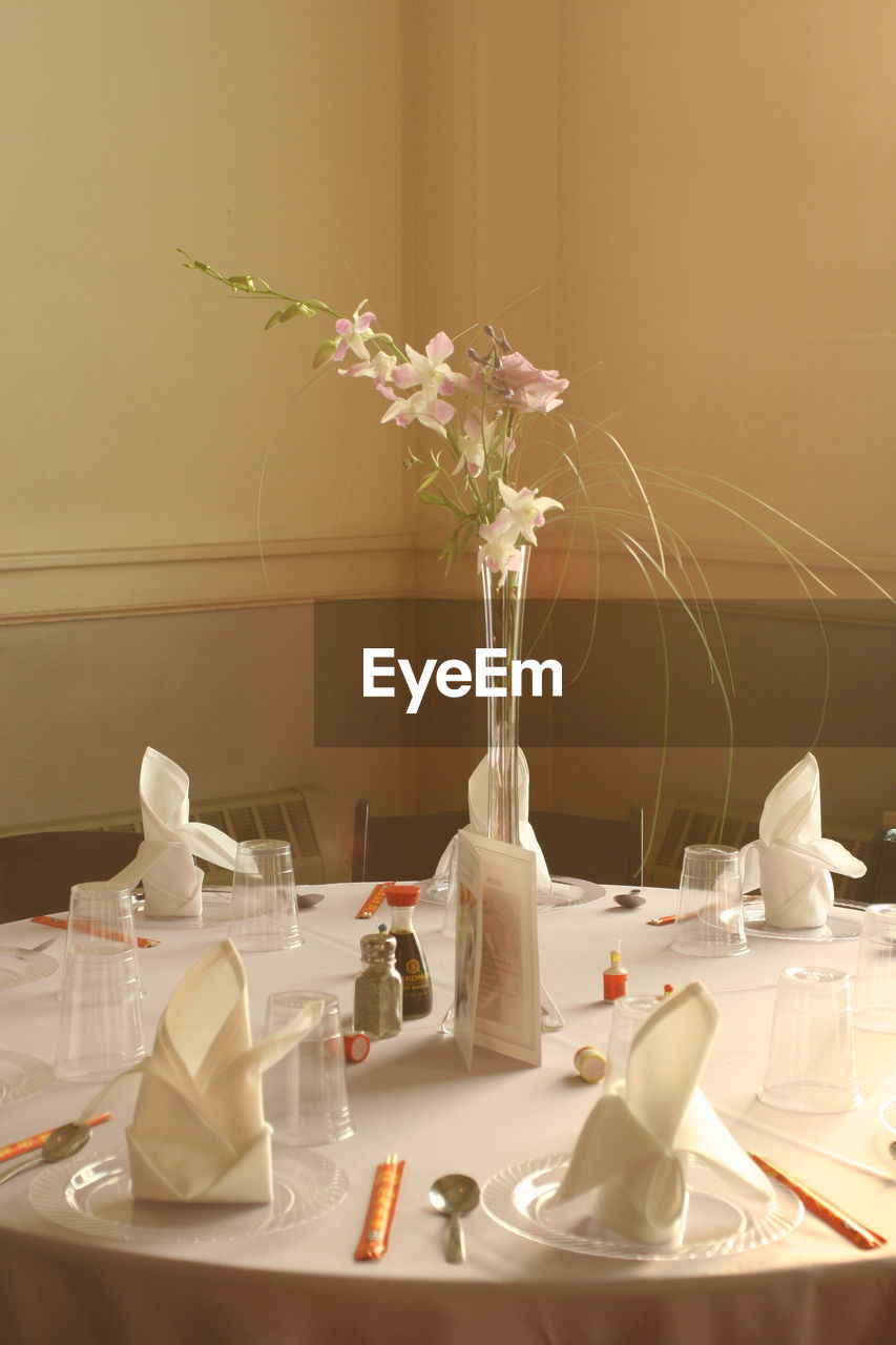 table, plate, vase, indoors, white color, no people, napkin, dining table, bottle, place setting, flower, tablecloth, close-up, day, freshness