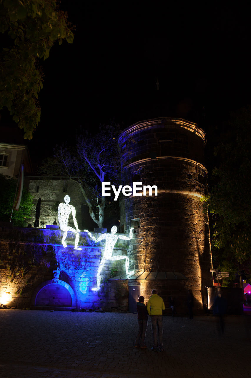 night, real people, illuminated, architecture, group of people, nature, human representation, art and craft, building exterior, sculpture, group, representation, people, long exposure, tree, creativity, motion, men, statue, city, outdoors