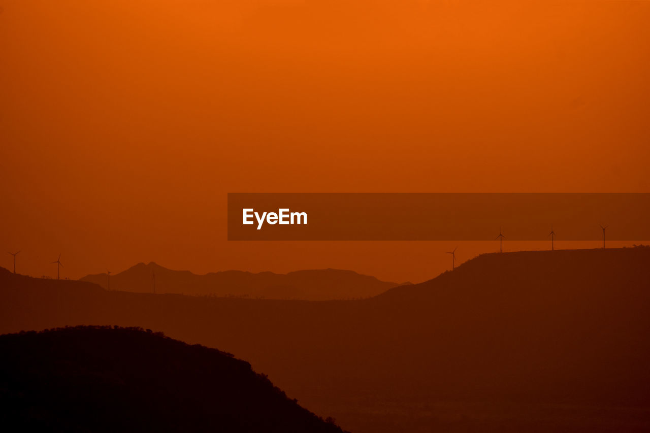 scenics - nature, beauty in nature, tranquil scene, sky, tranquility, sunset, orange color, mountain, environment, silhouette, non-urban scene, landscape, copy space, idyllic, nature, land, no people, remote, outdoors, mountain range, romantic sky