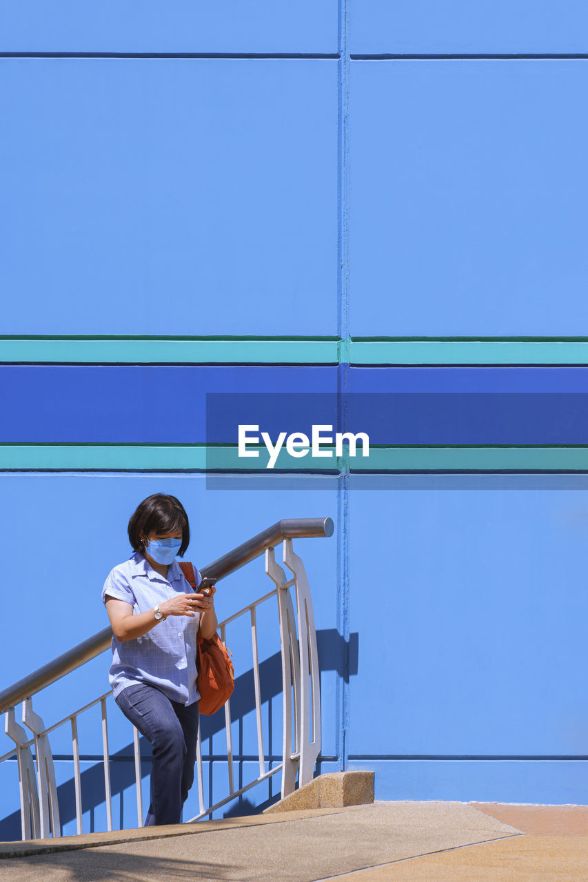 Asian woman using smartphone while walking up staircase outside of shopping mall